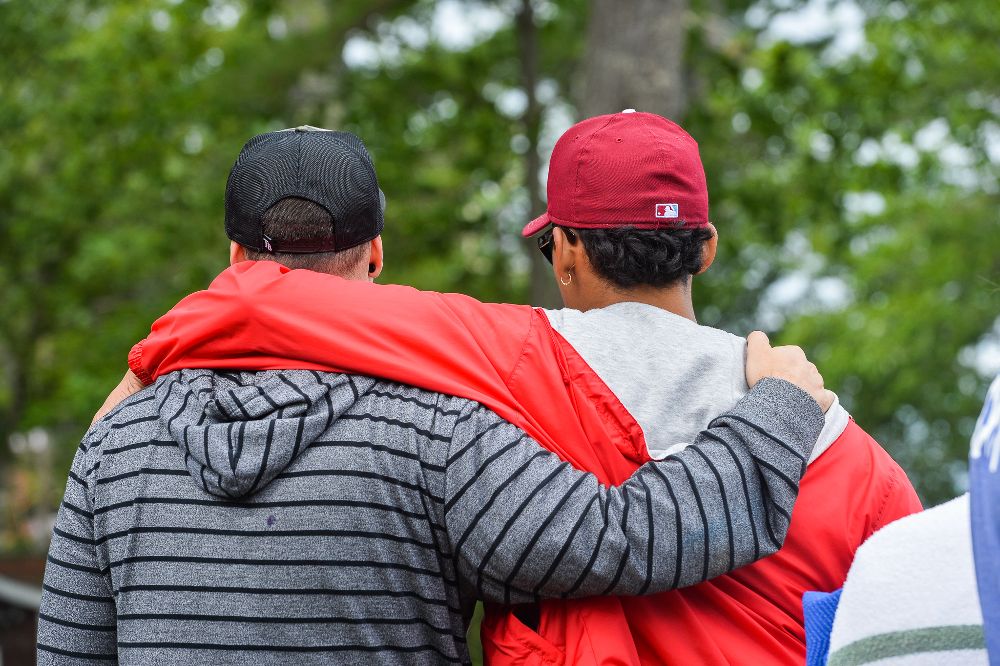 Two campers walking arm in arm at ManEx, a clinically-informed summer camp for grieving children who have lost a parent, sibling, or caregiver.