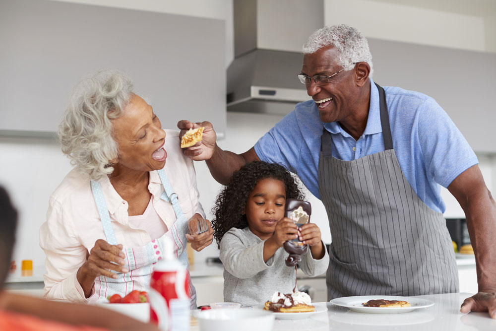 Grandparents cooking in the kitchen with their granddaughter.