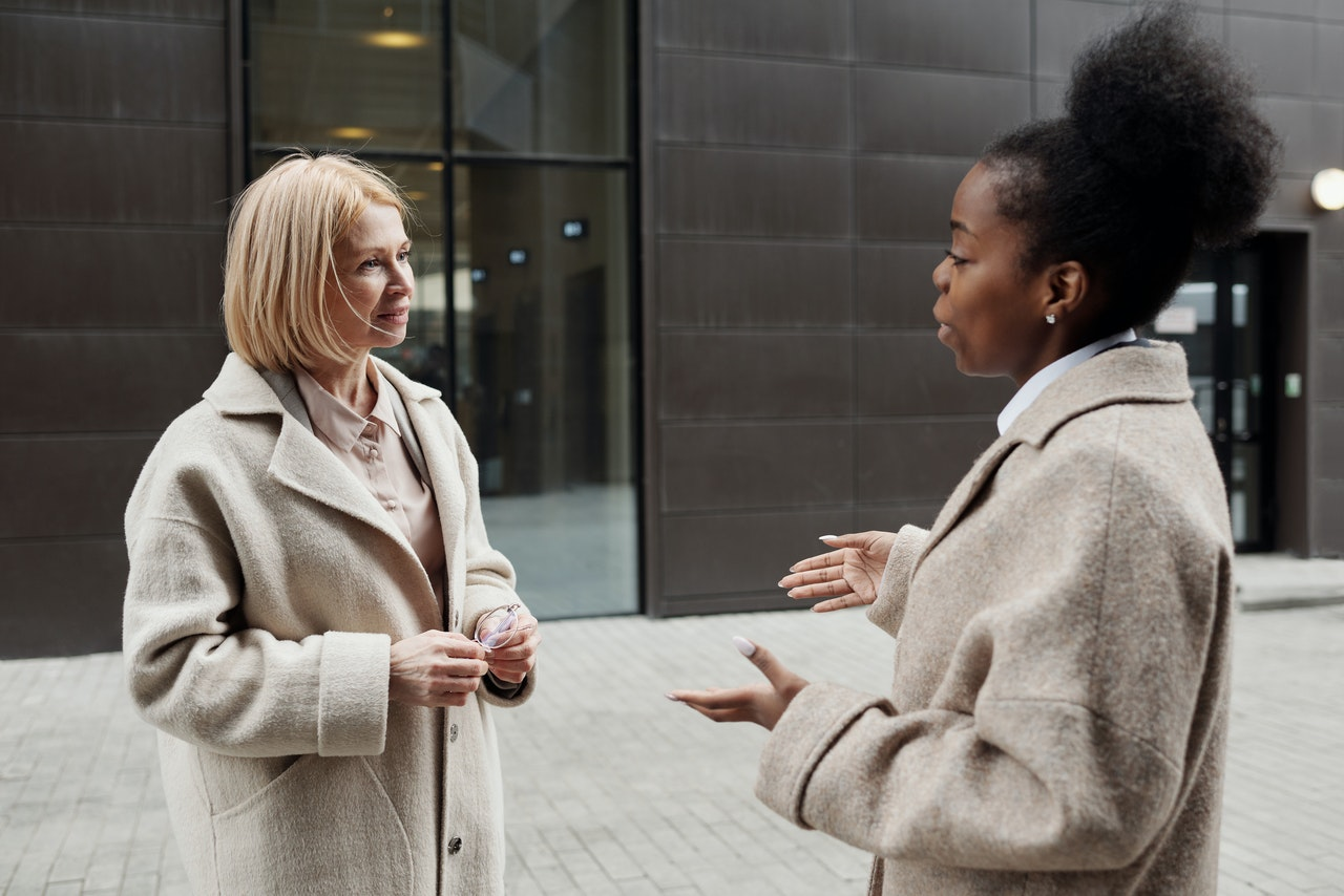 A caucasian women speaking with a black American woman both in business attire