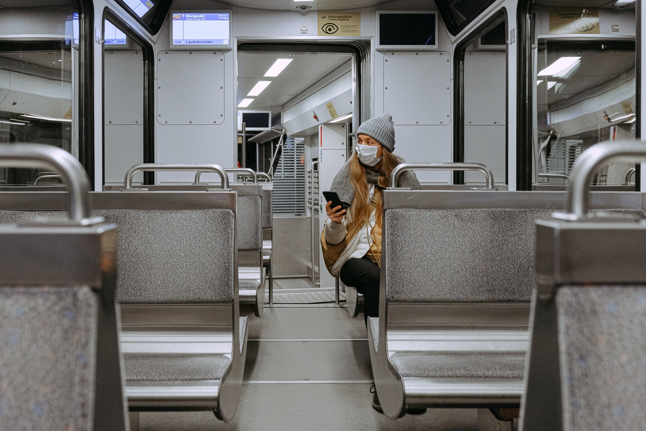 A woman with surgical mask, sitting on a metro train