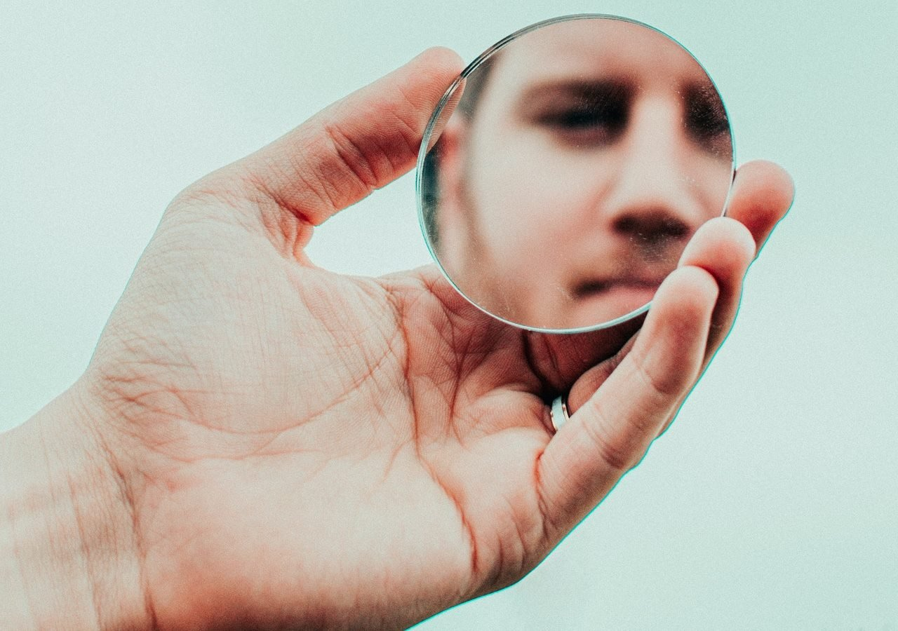 A man looking on the reflection of himself on a small round mirror
