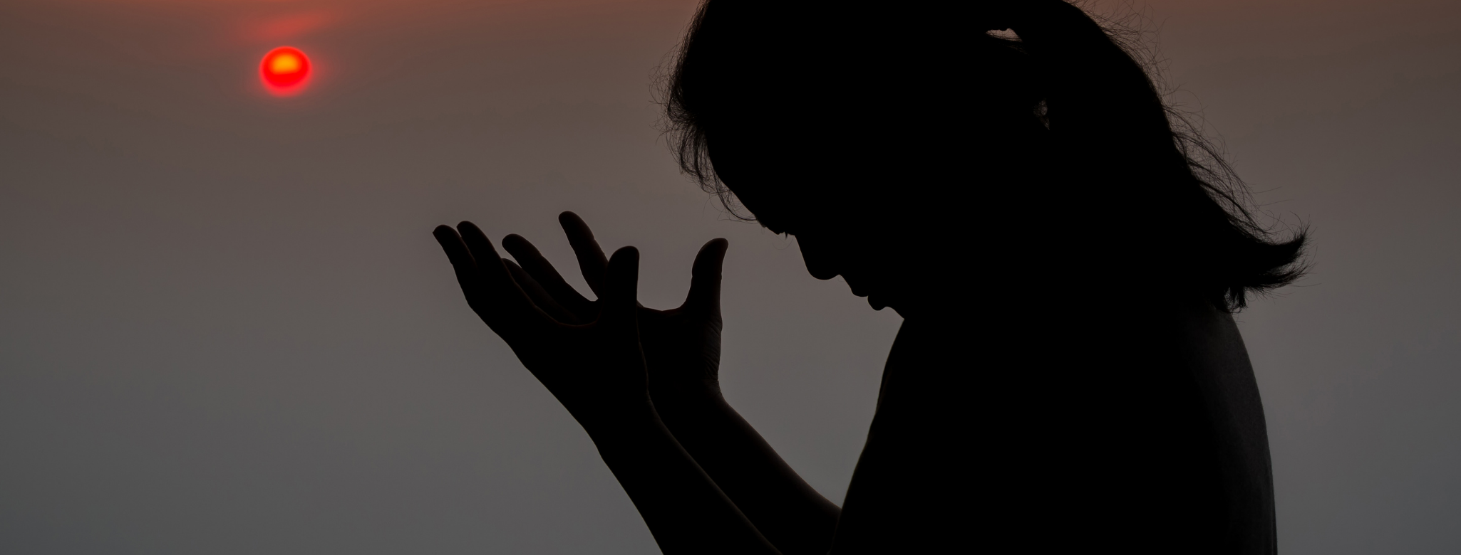 Woman at sunset with head bowed in prayer or meditation