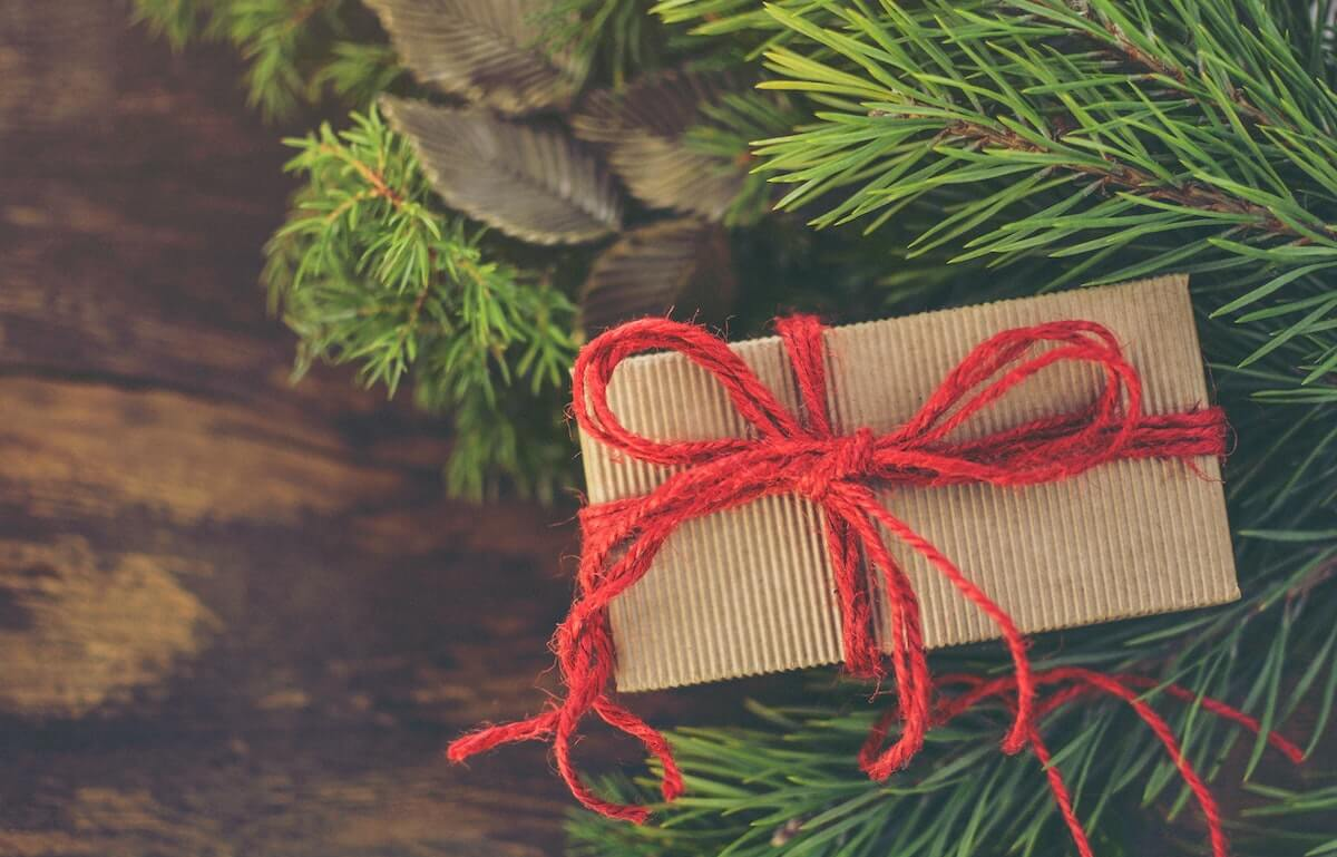 brown paper wrapped gift with red string ribbon sitting underneath Christmas tree branches