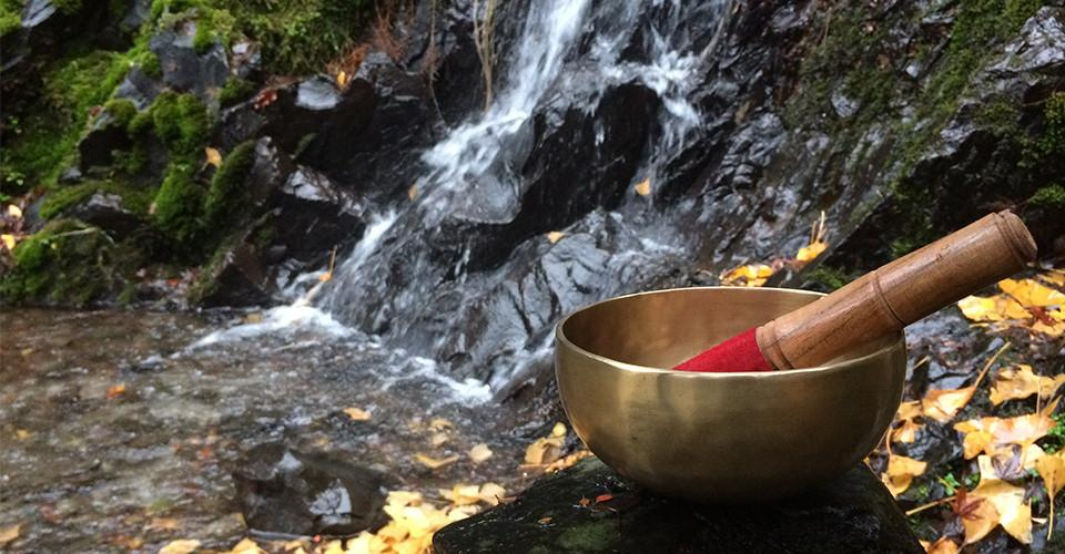 singing bowl resting on a rock by a waterfall