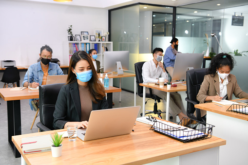 Workers practicing social distance and wearing of masks in the office
