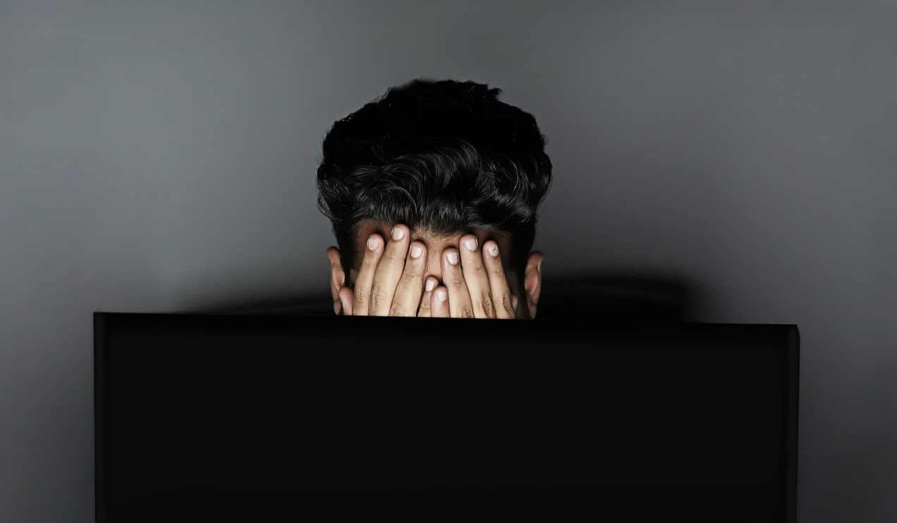 Overwhelmed and exhausted adult in front of computer