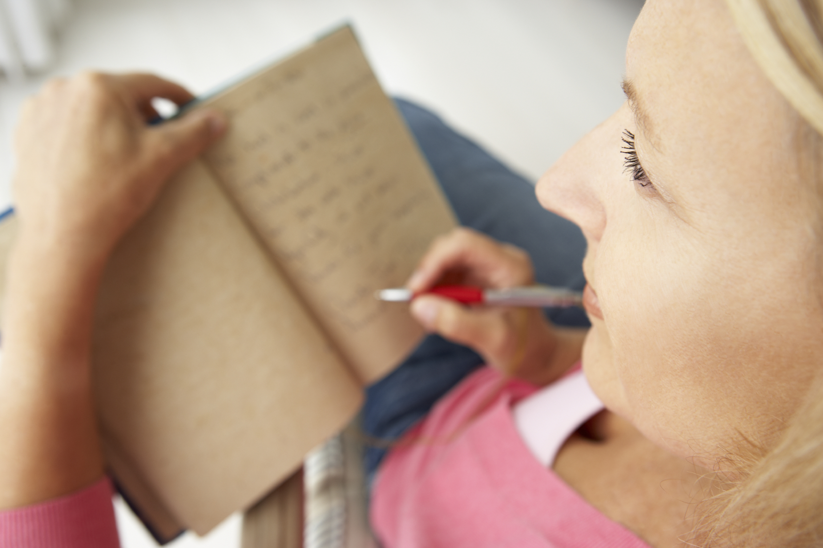 Senior woman writing in notebook