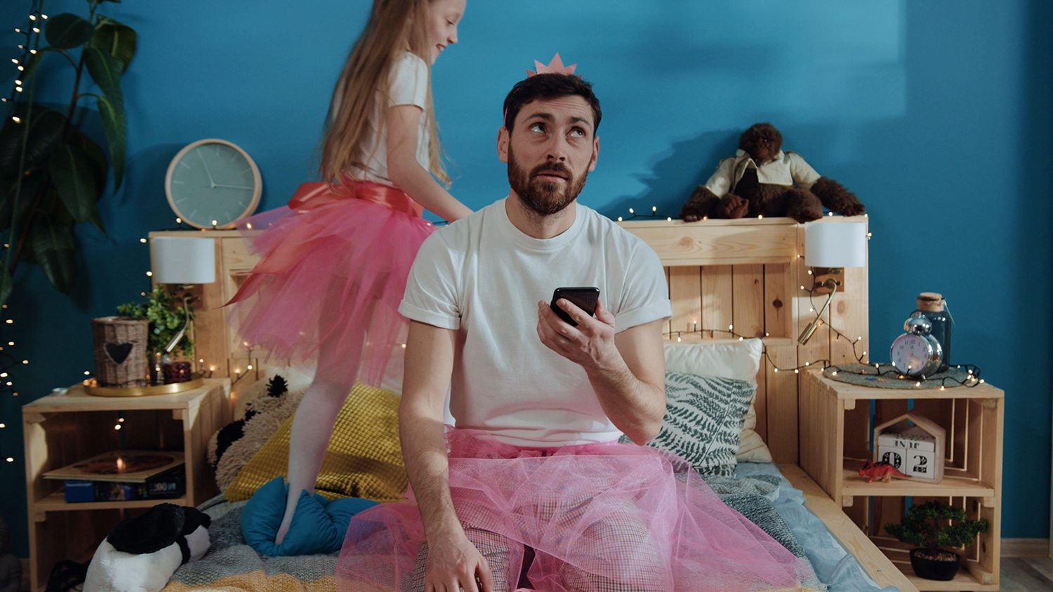 Portrait of tired bored young man in fairy dress using a smartphone sitting on bed. Happy princess girl dancing around waving magic wand playing with her daddy at home.
