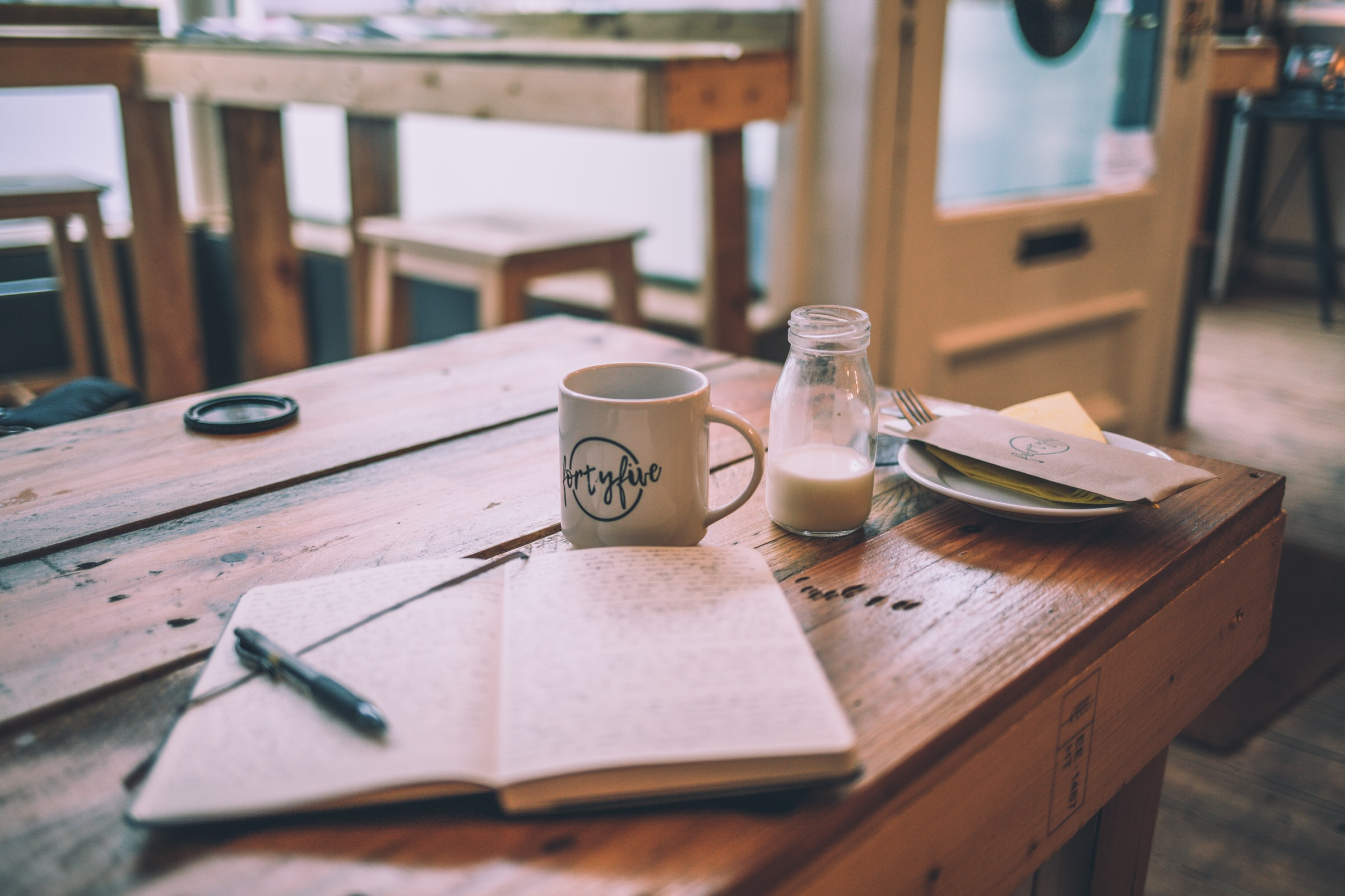 White diary behind a milk bottle and coffee mug