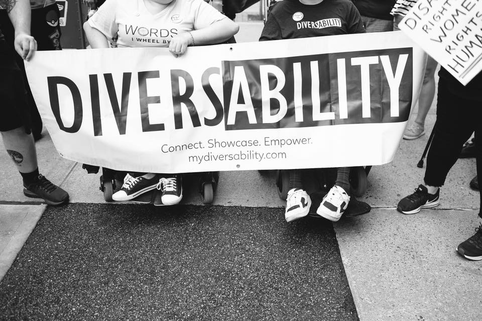 A black and white photograph of Diversability community members holding the Diversability sign. Two of the members are sitting in wheelchairs. It is a close up image of the banner, with the community member's heads cropped out.