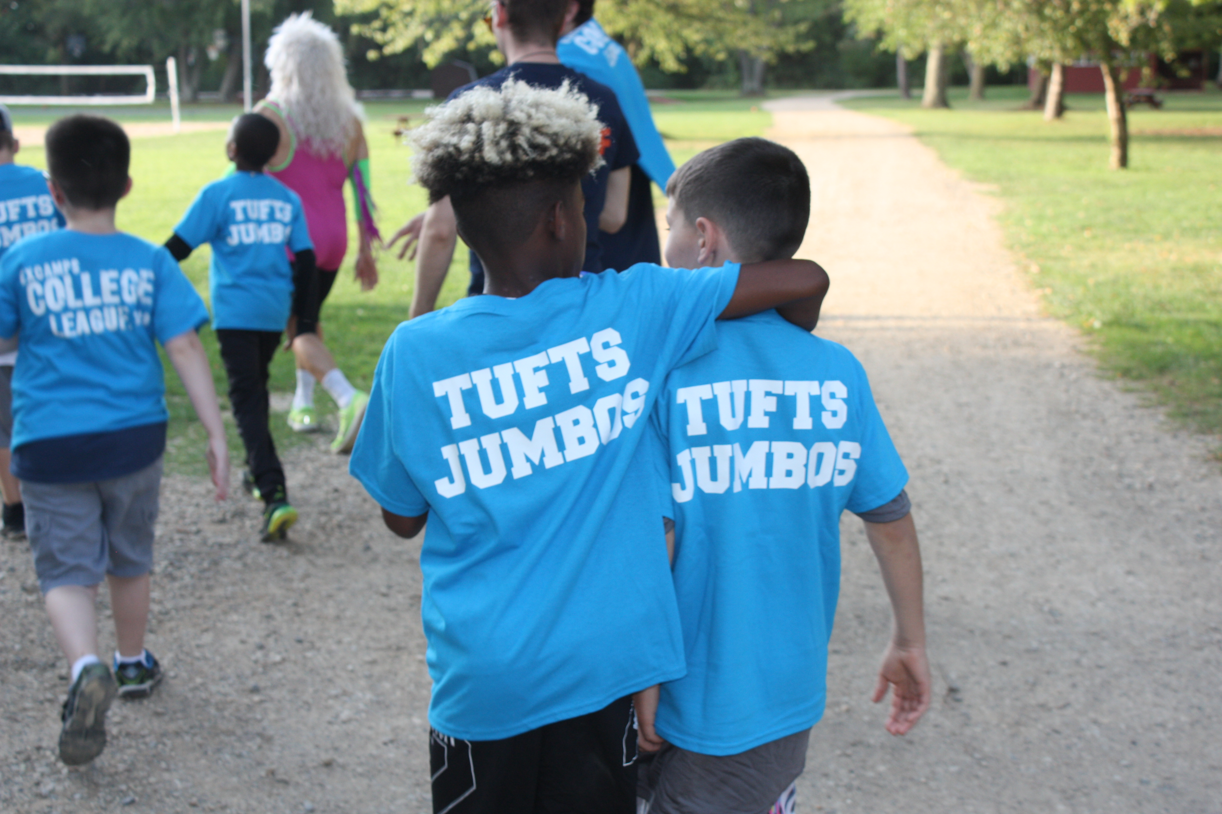 Two campers walking arm in arm at Experience Camp.