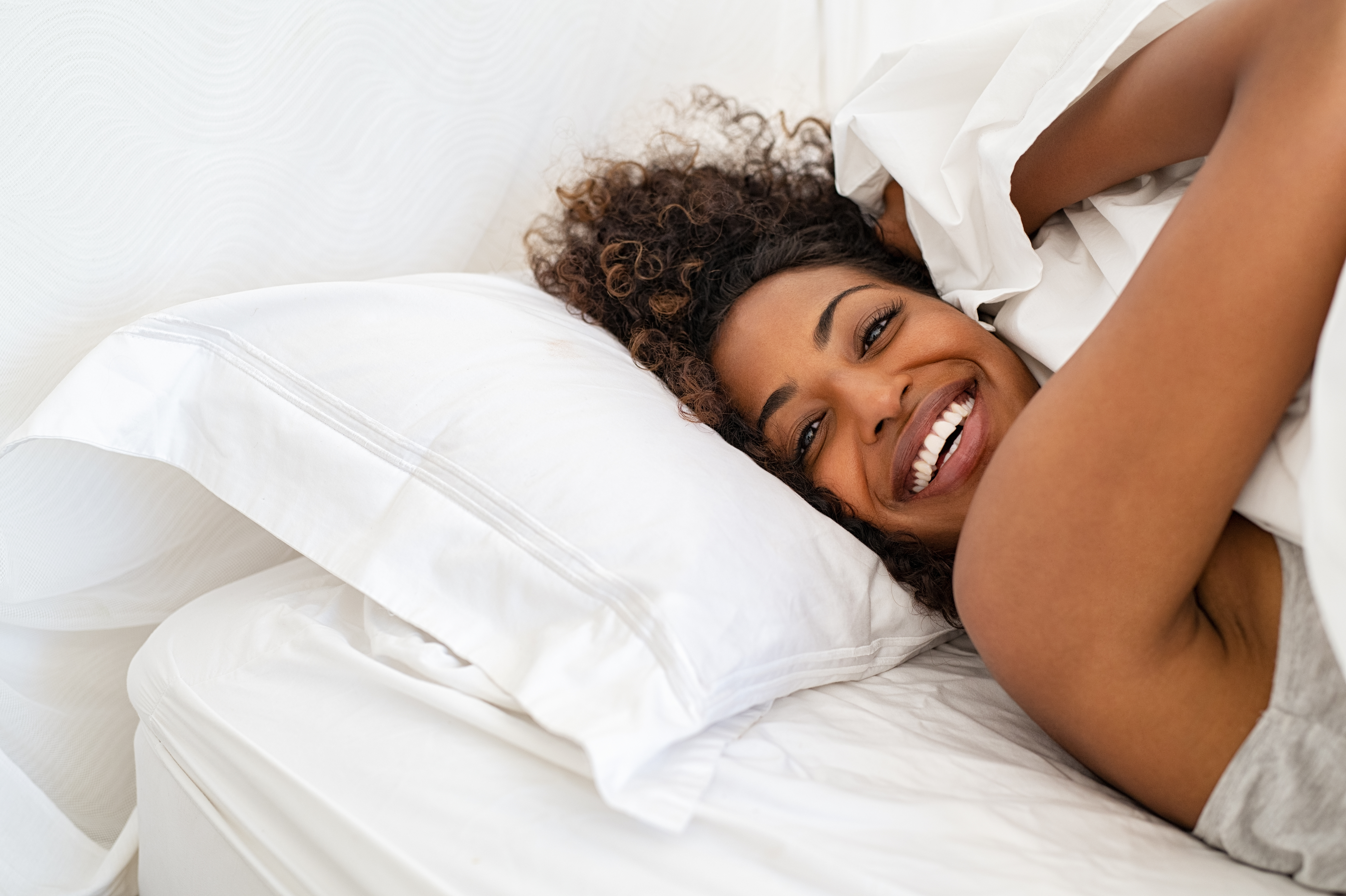Cheerful young woman lying on bed playing with blanket and looking at camera. African girl feeling fresh after nap on white bed with copy space. Laughing woman having fun while embracing pillow and blanket.