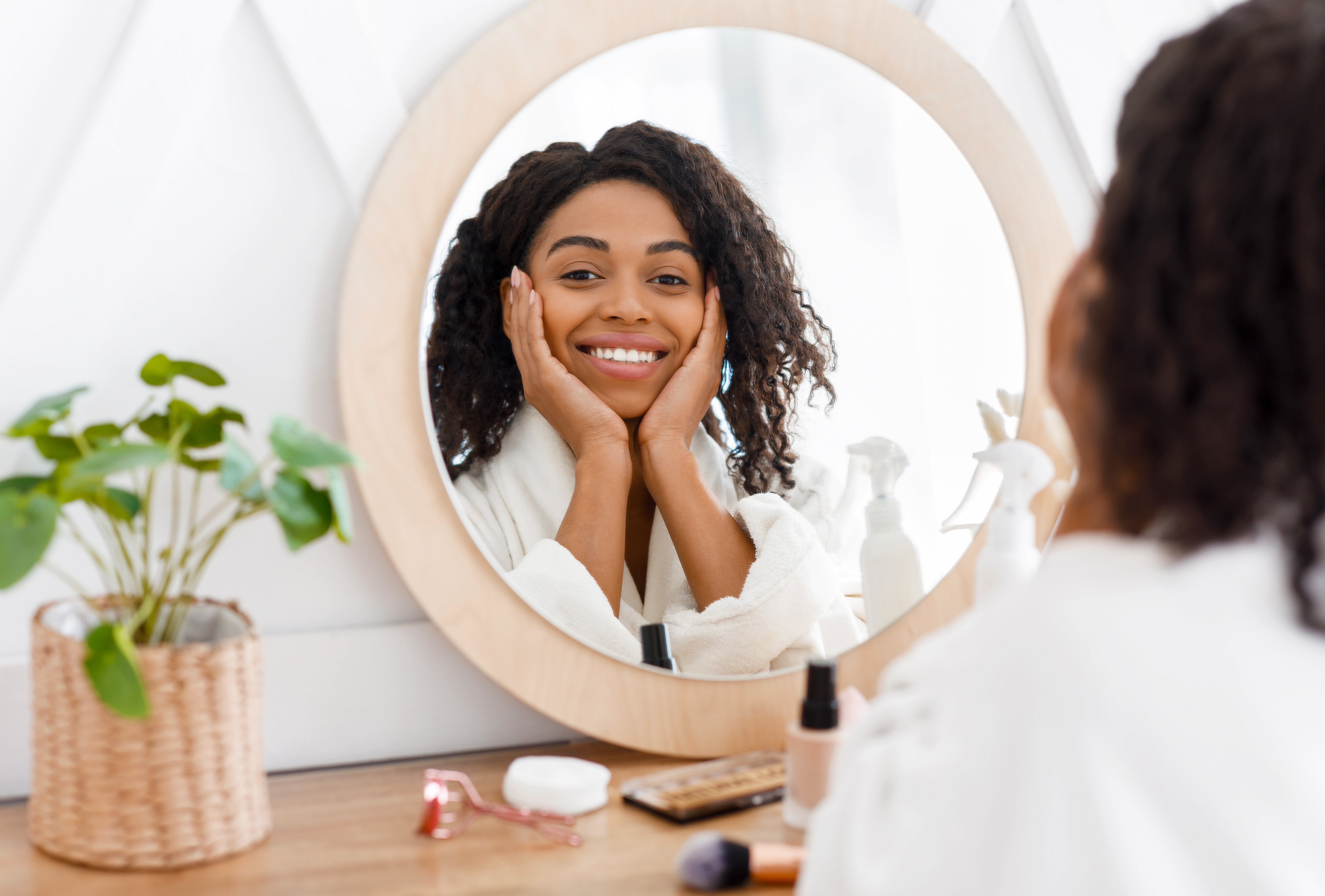 Self-Care. Beautiful African American Woman In Bathrobe Ready To Apply Makeup, Reflecting In Mirror Of Toilette Dresser Table, Looking At Camera