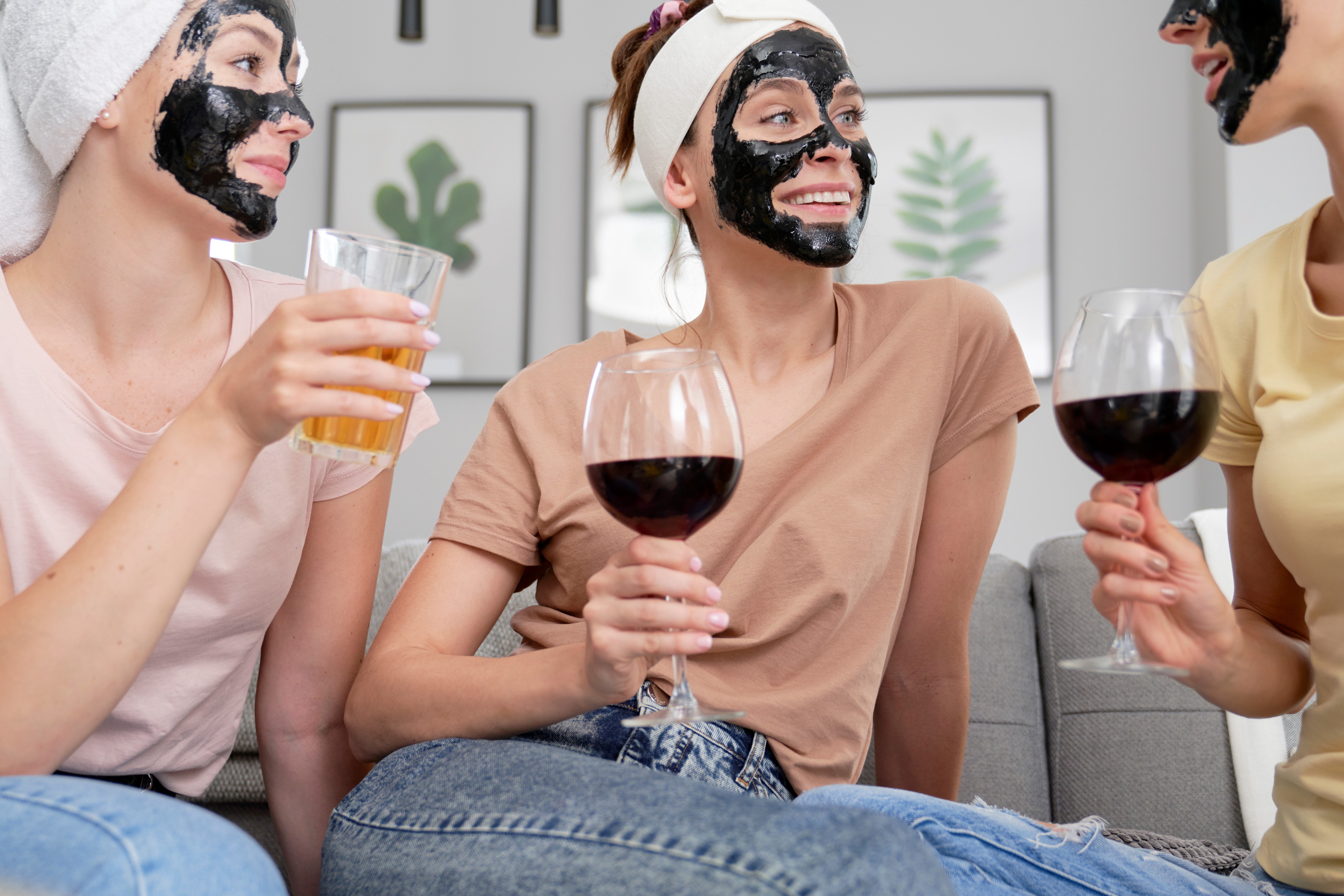 women drinking wine while having a beauty treatment