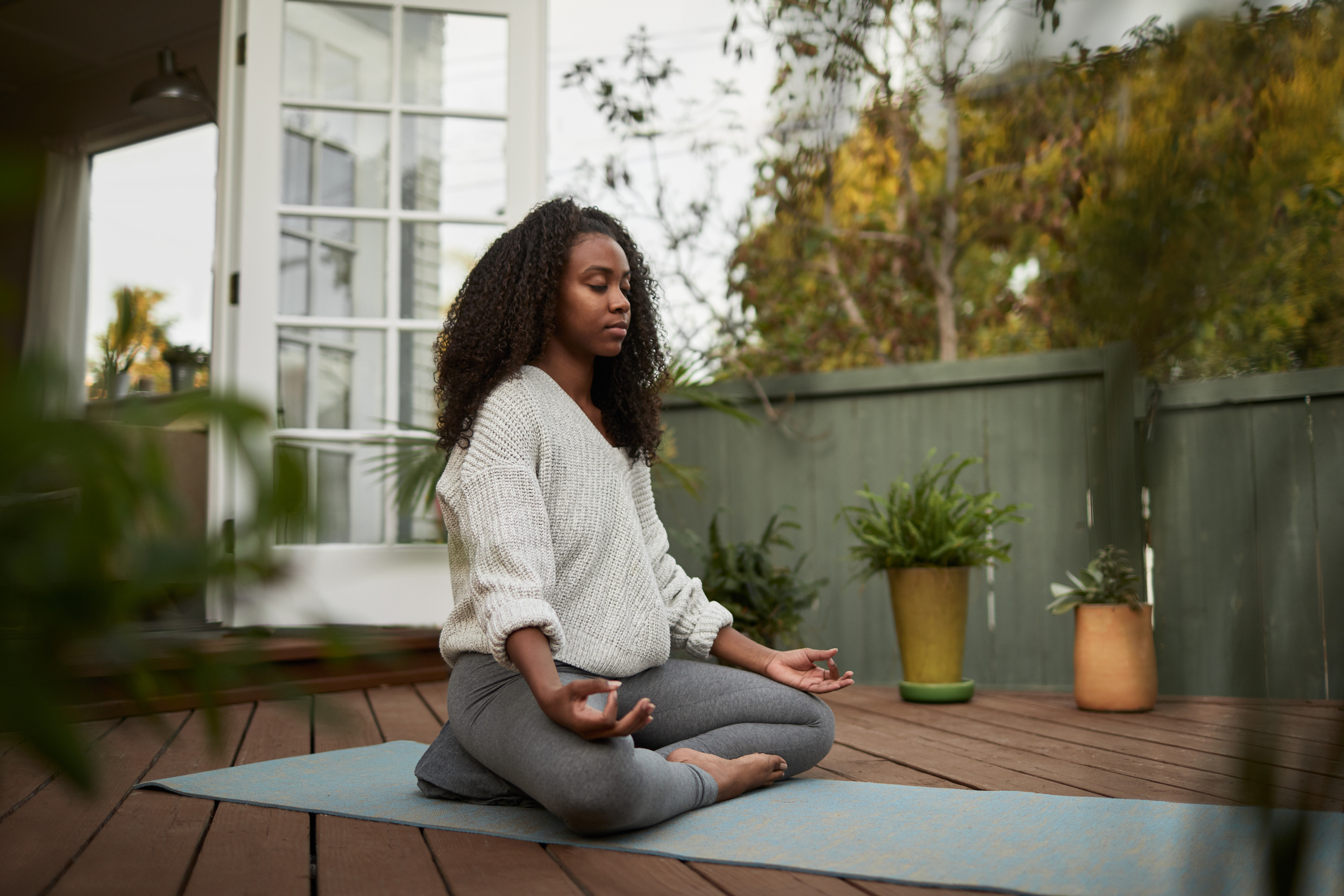 Young African American woman sitting on exercise mat outside on her patio and meditating in the lotus pose during a yoga session