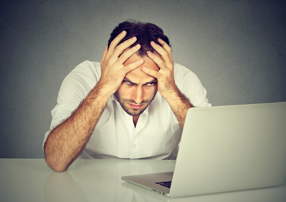 Too much work to do. Stressed young man sitting at his desk in front of computer in office. Busy schedule in college, workplace, sleep deprivation concept