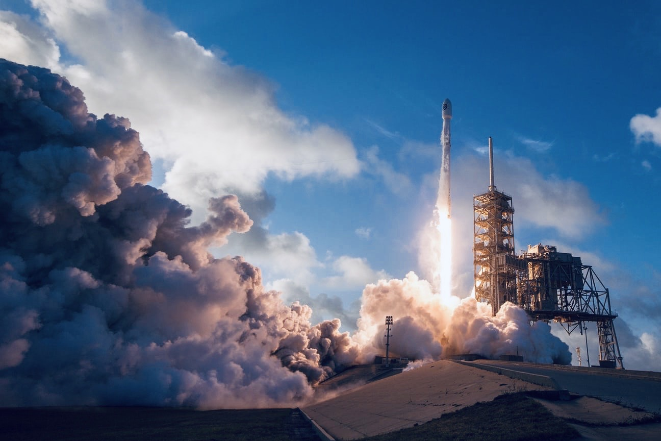 Rocket Launching into blue skies surrounded by billowing clouds of white smoke