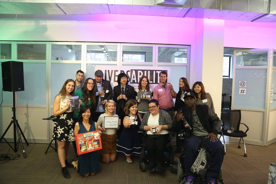 The Diversability community at a holiday gathering in 2015 with each person holding their gift.