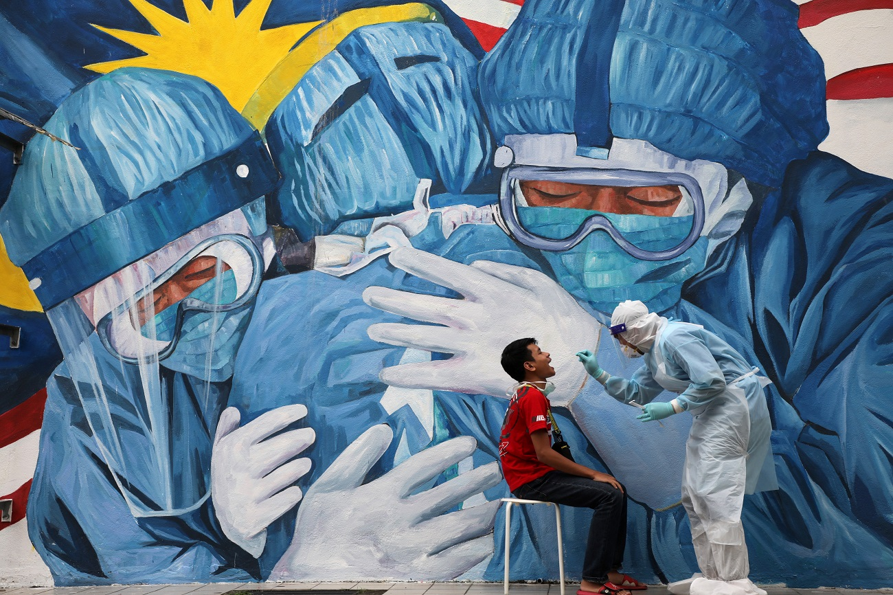 A doctor collects a swab sample from a man to be tested for the coronavirus disease (COVID-19) outside Clinic Ajwa in Shah Alam, Malaysia December 10, 2020. REUTERS/Lim Huey Teng TPX IMAGES OF THE DAY
