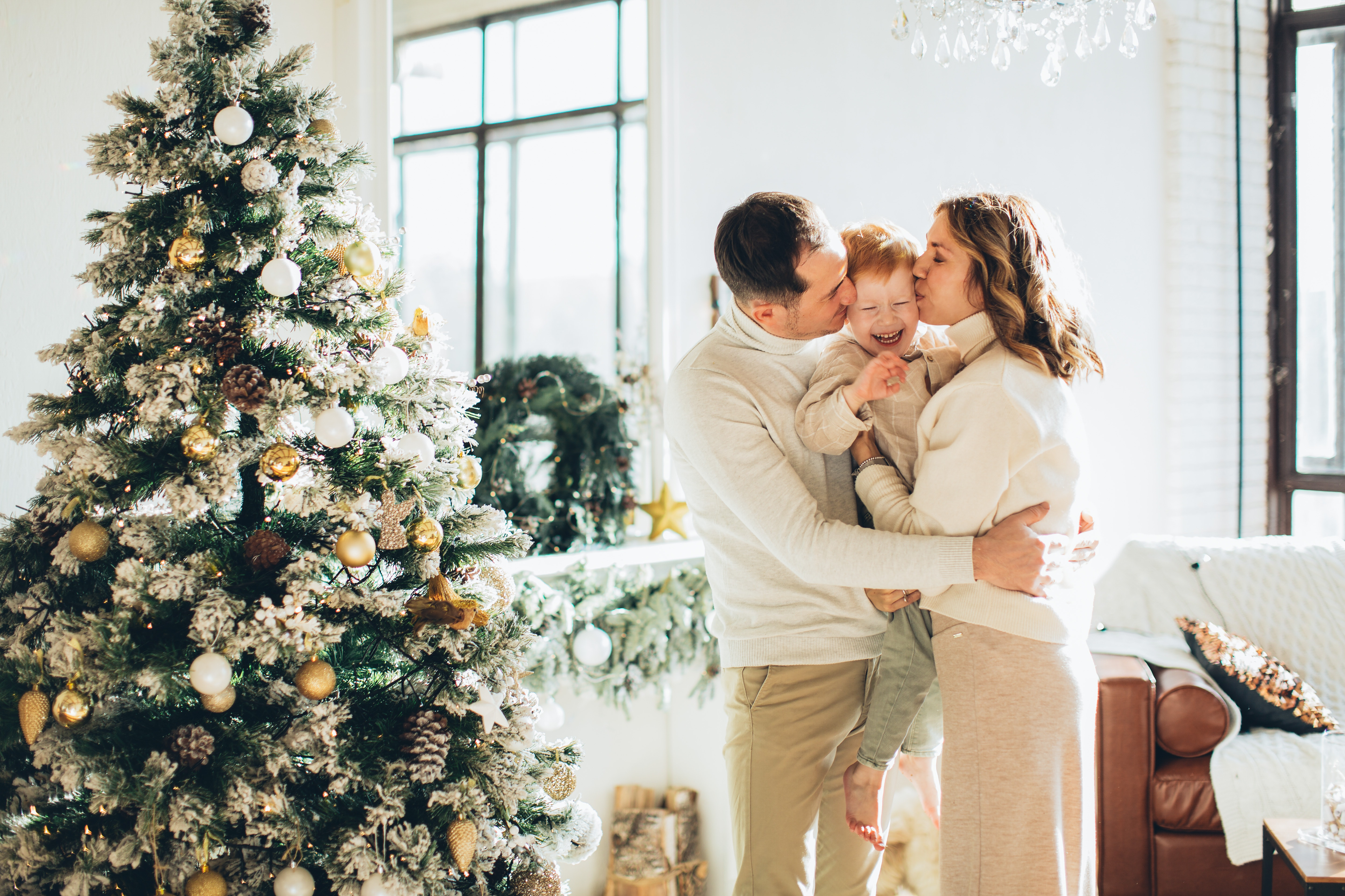 Parents and child by Christmas tree