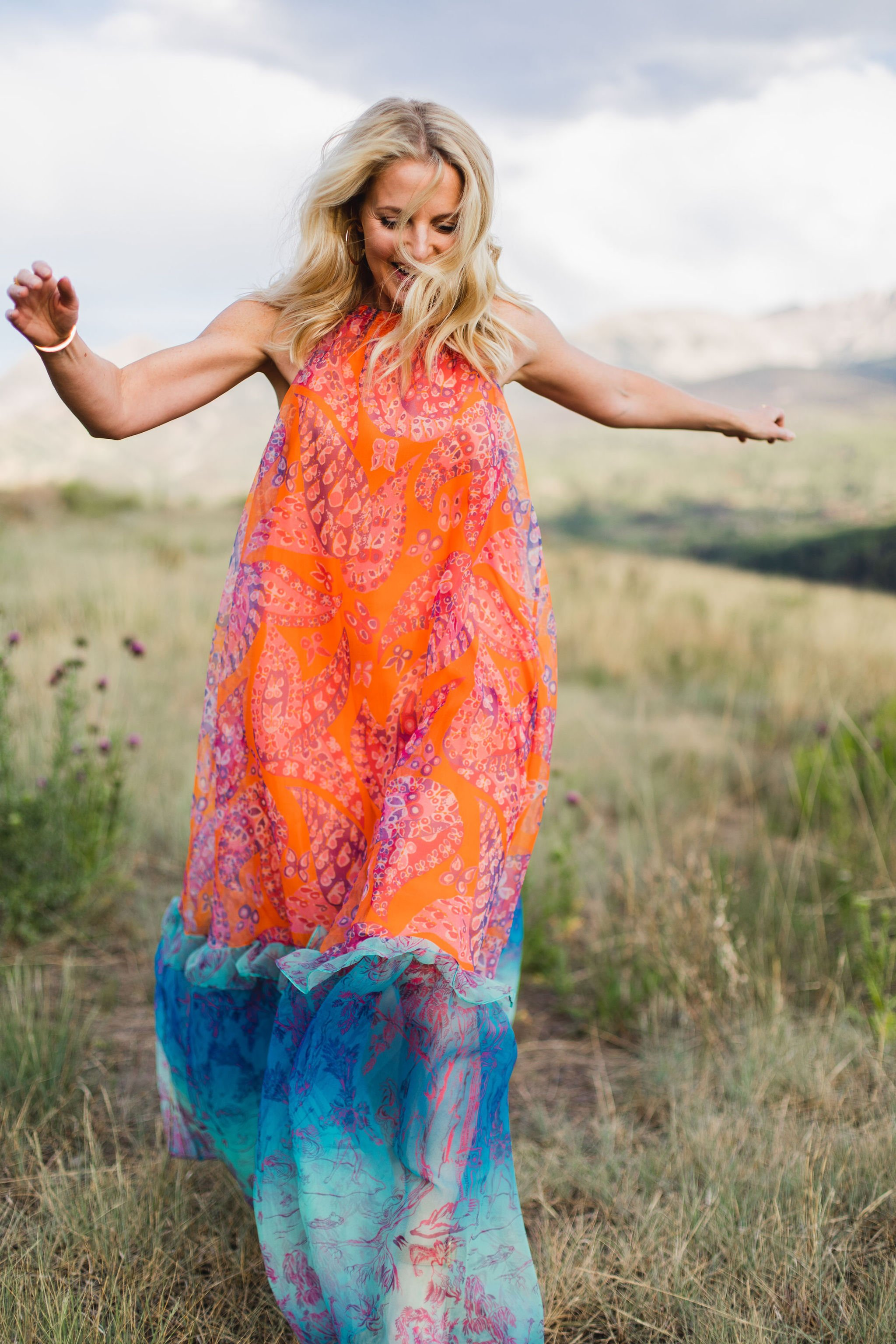 blonde woman wearing trapeze dress in bright colors running through grassy field