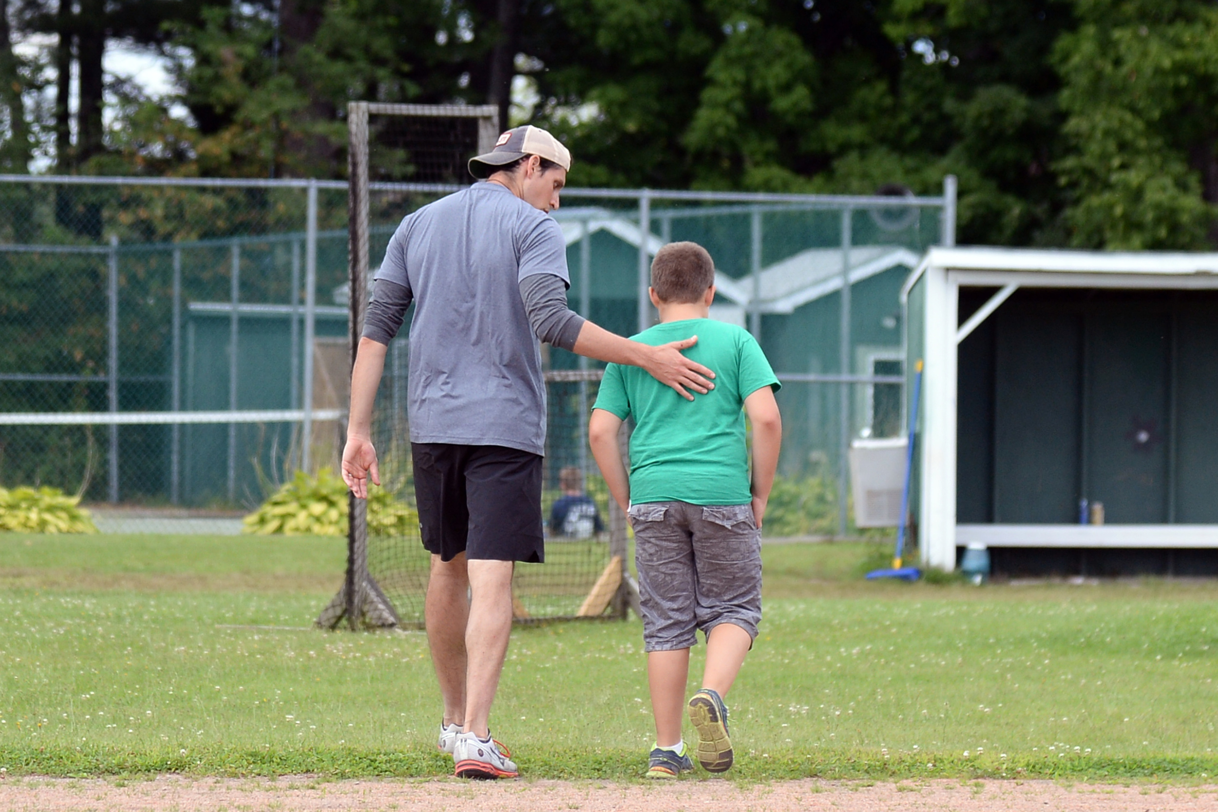 A volunteer consoling a grieving camper as they walk at Experience Camps.