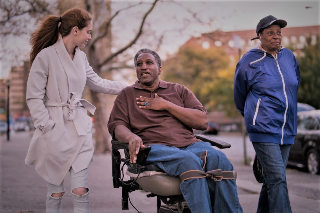 The White teenager girl talking with disabled wheel-chaired African American man and woman when they walking on the street in Bronx, New York, together