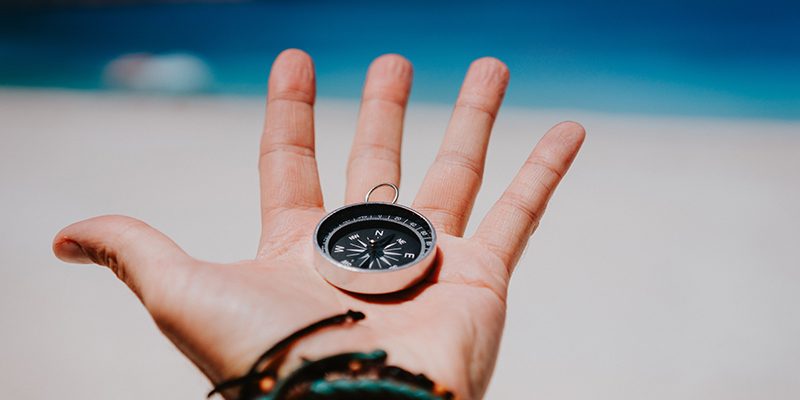 Open palm with stretched fingers holding black metal compass against white sandy beach. Find your way or goal concept. Point of view pov.