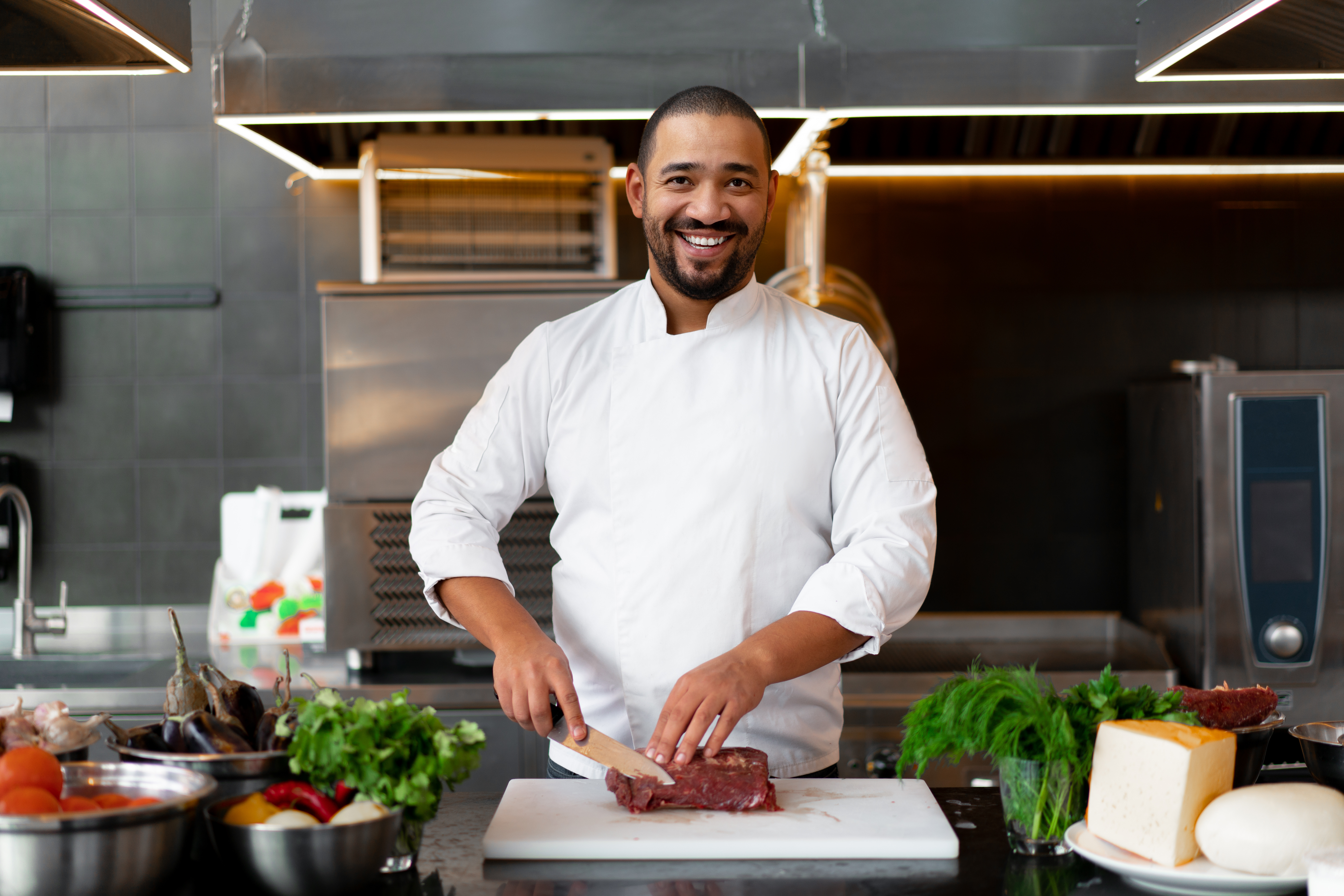 Handsome young African chef standing in professional kitchen in restaurant preparing a meal of meat and cheese vegetables. Portrait of man in cook uniform Cuts meat with a metal knife.