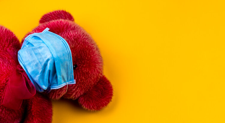 Lonely Red Teddy bear in a protective medical mask on a yellow background with respiratory masks. Coronavirus covid-19 prevention concept.