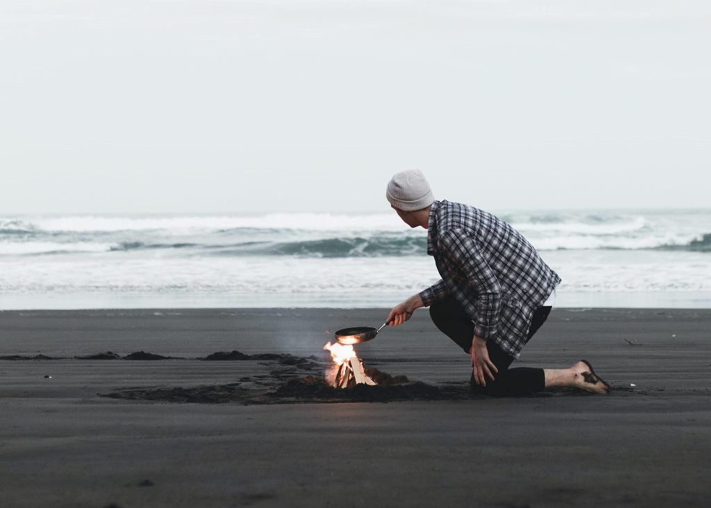 A man cooking on a camp fire in front of a beach