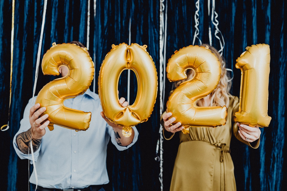 A couple holding 2021 gold balloons