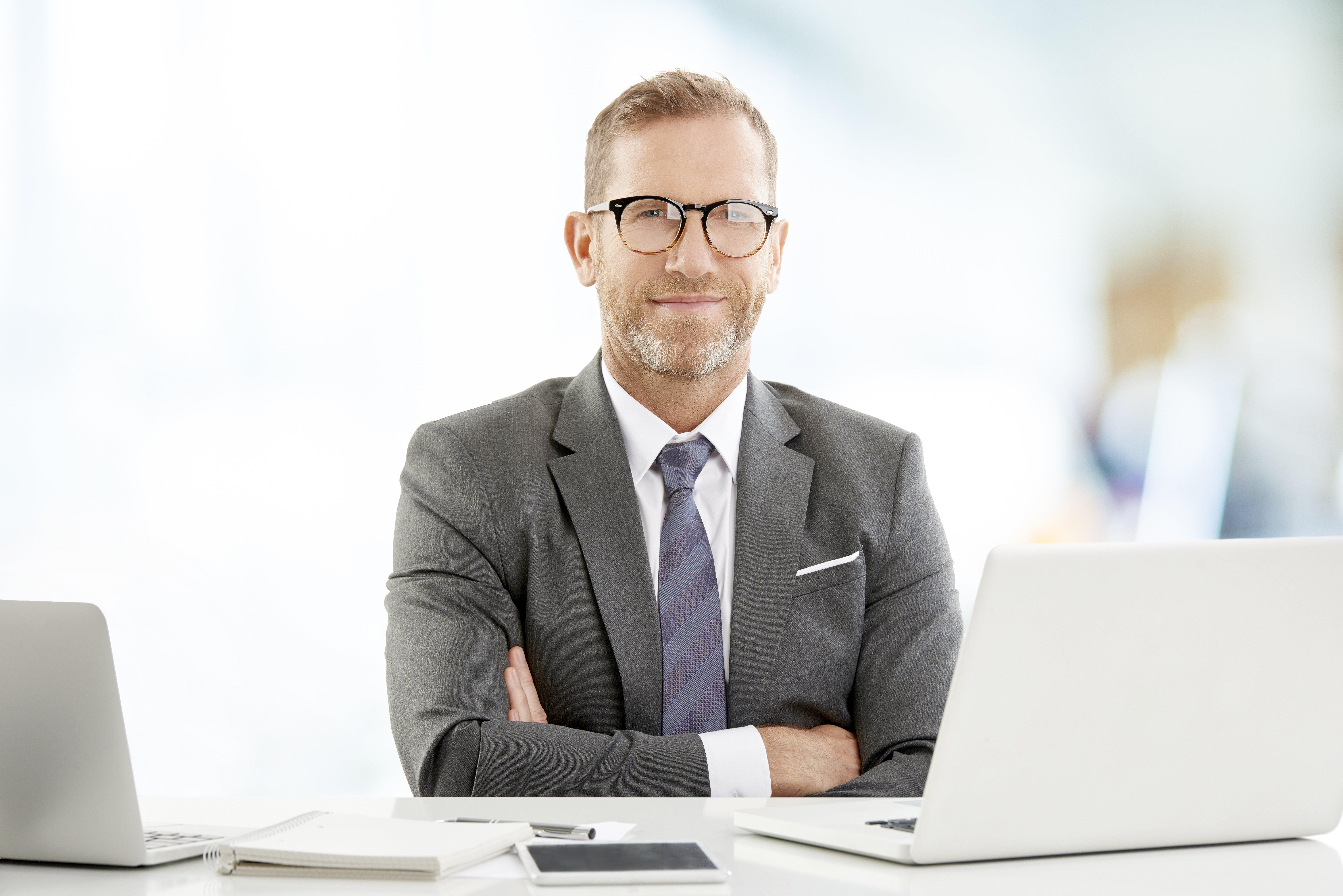 Executive businessman with arms crossed sitting at the office desk and looking at camera.