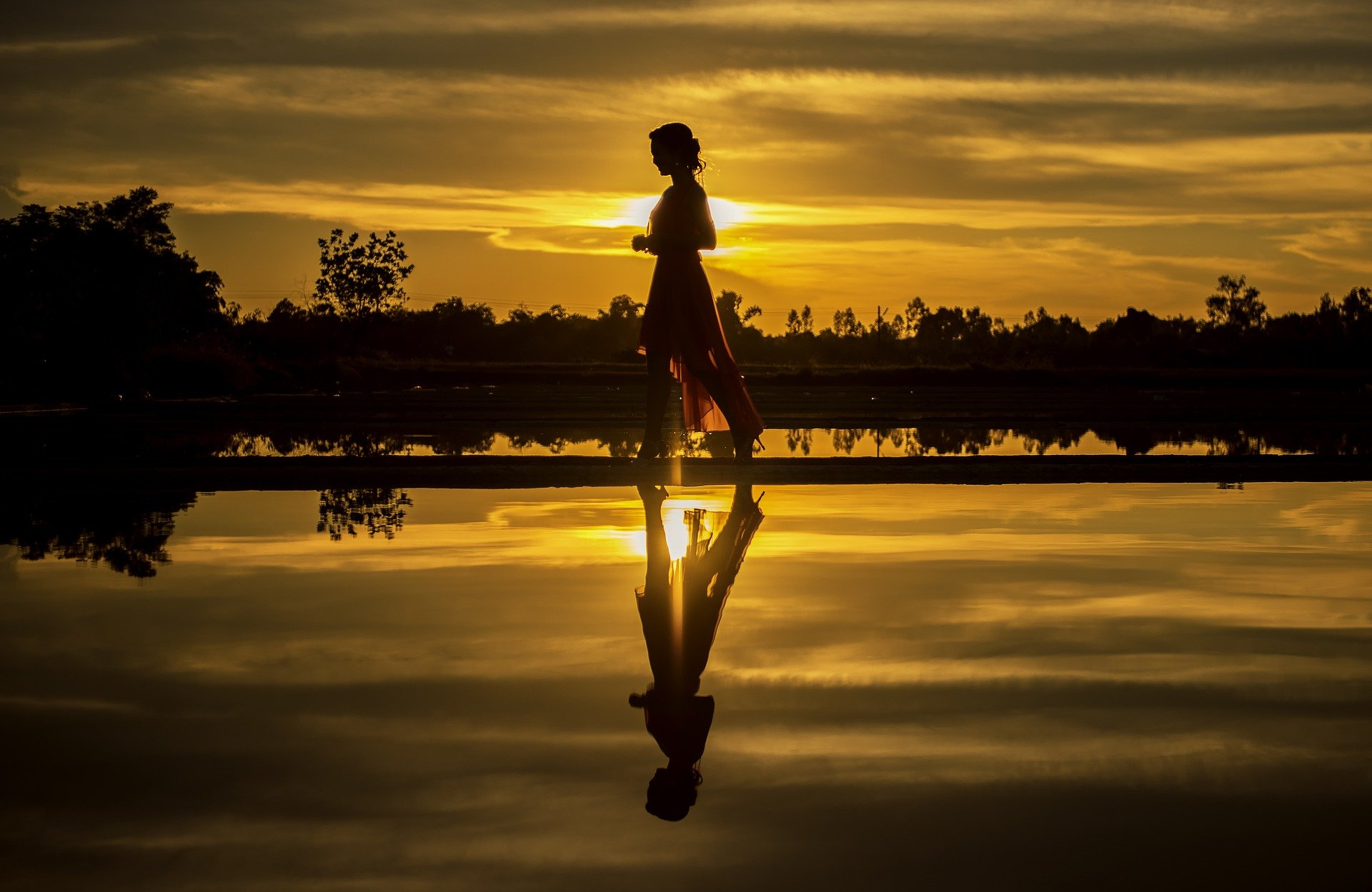 a woman walking with the orange and golden sunset behind her