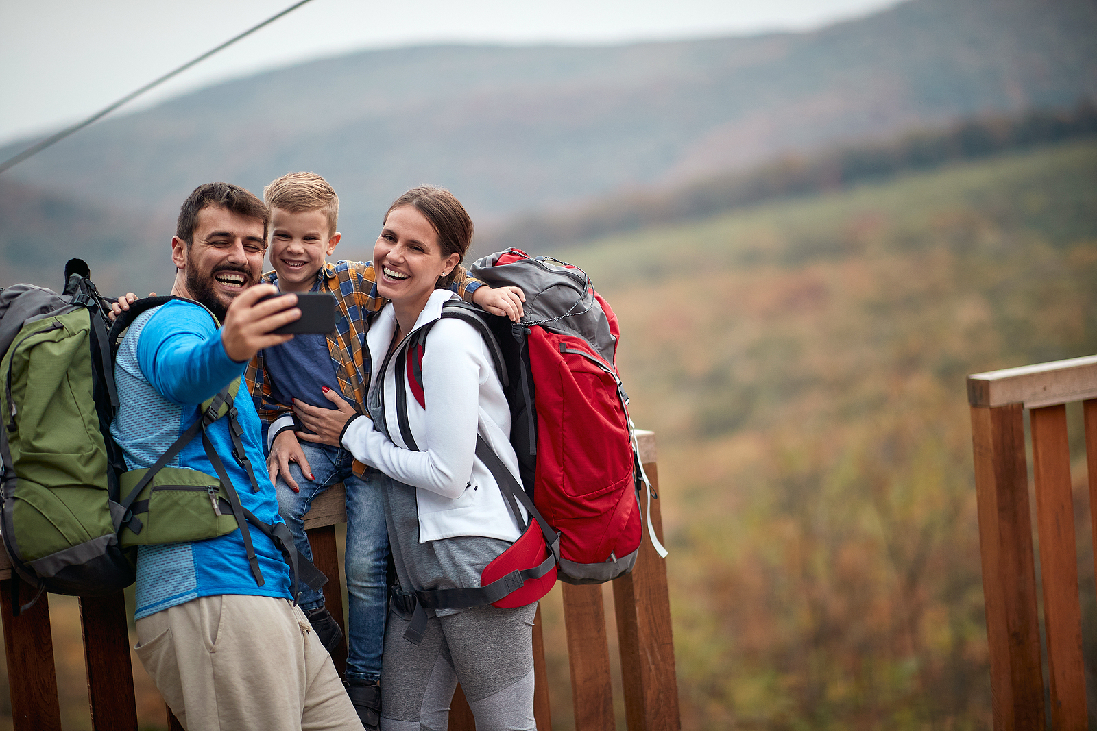 Happy couple with a son on a hiking adventure;Spring or autumn h