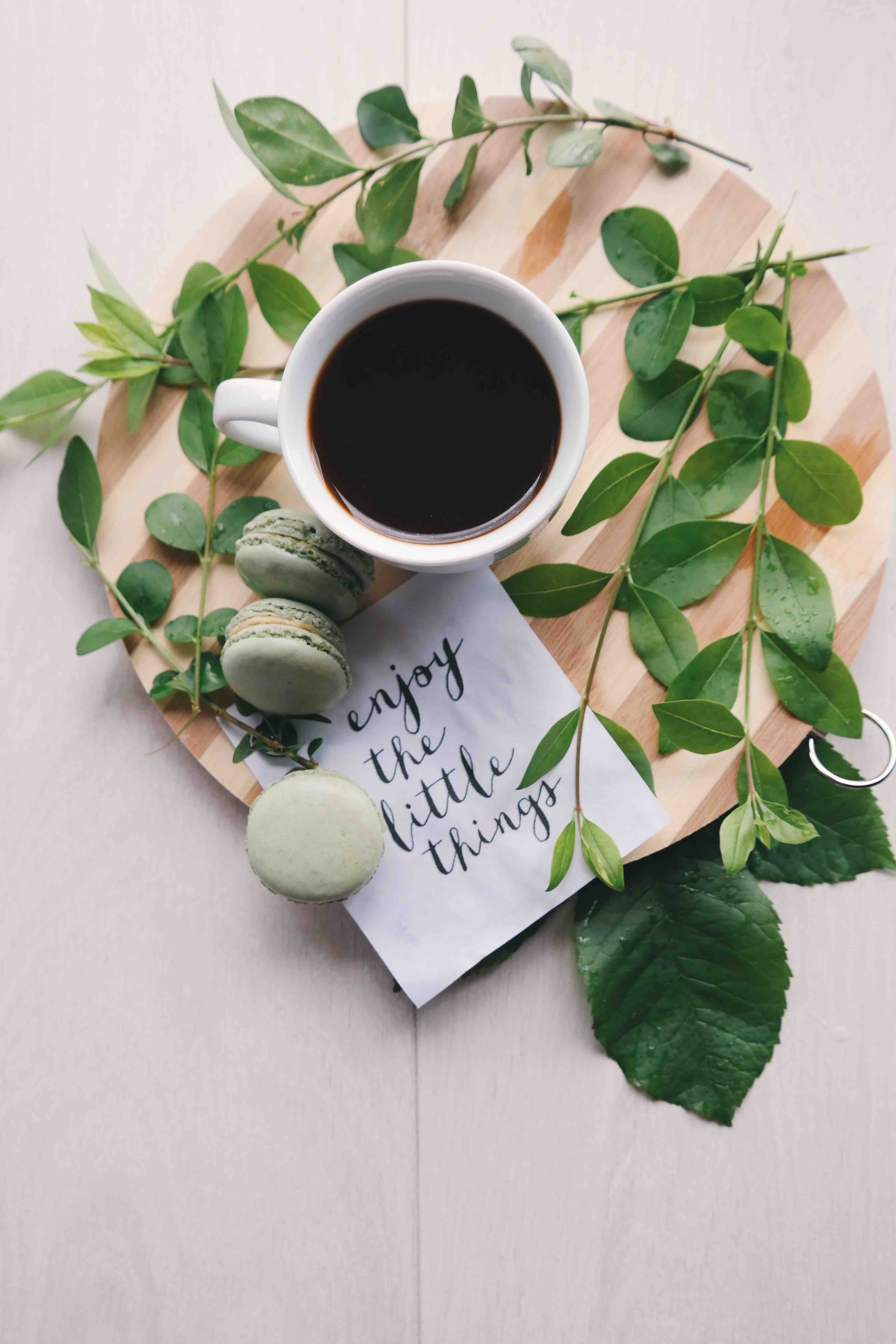"""cup of coffee on a wood board, with green leaves, macarons and a napkin that says """"Enjoy the little things."""""""