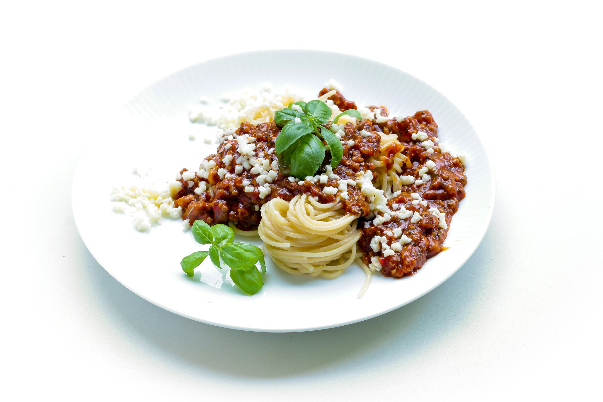 a plate of pasta with pasta sauce, herbs and cheese
