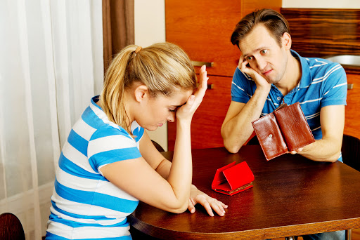 59093903 - worried couple sitting at the table with empty wallets.