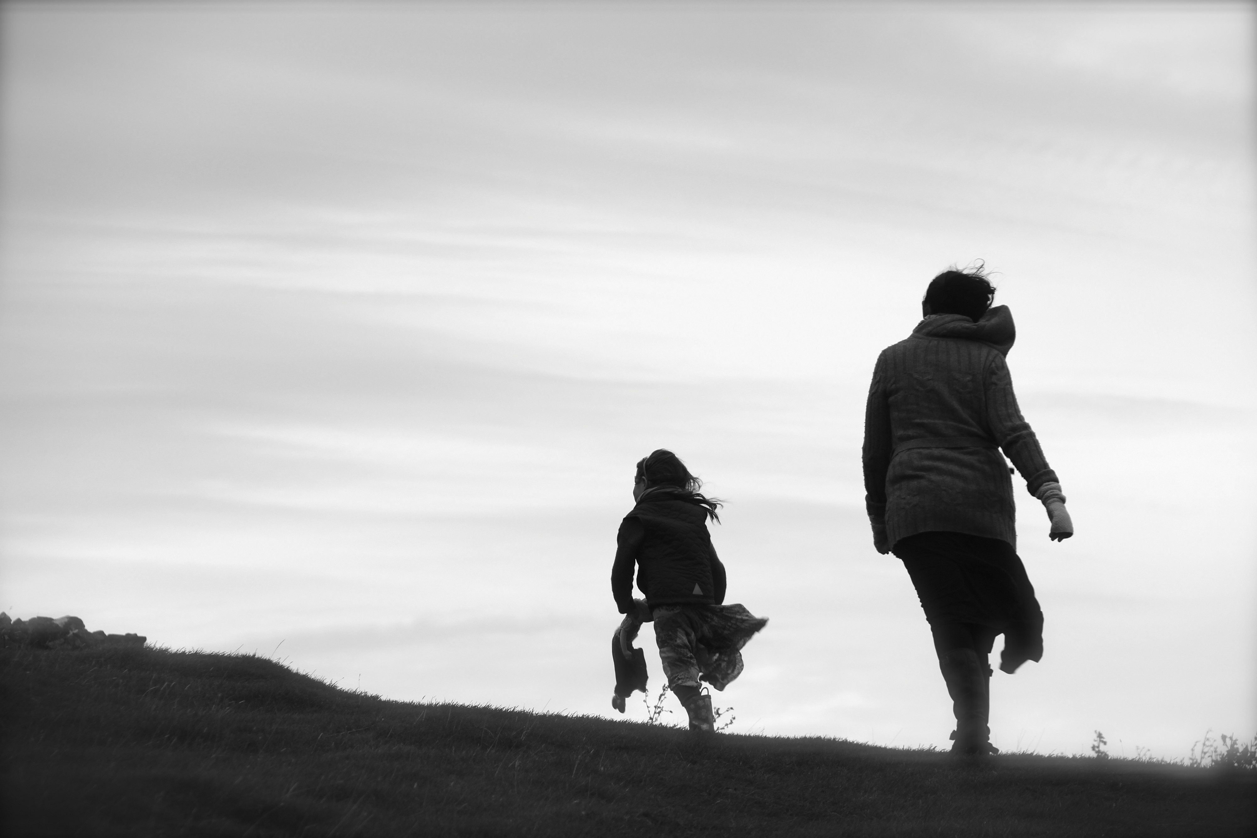 Black and white image of mother and daughter walking up hillside in silhouette.