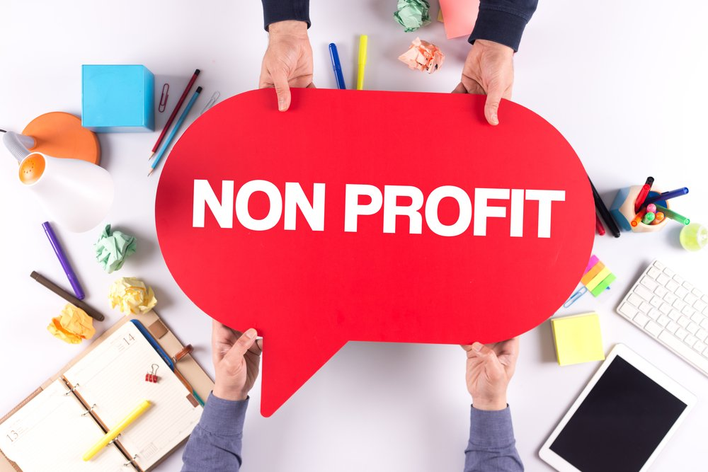 Two people holding speech bubble with NON PROFIT concept