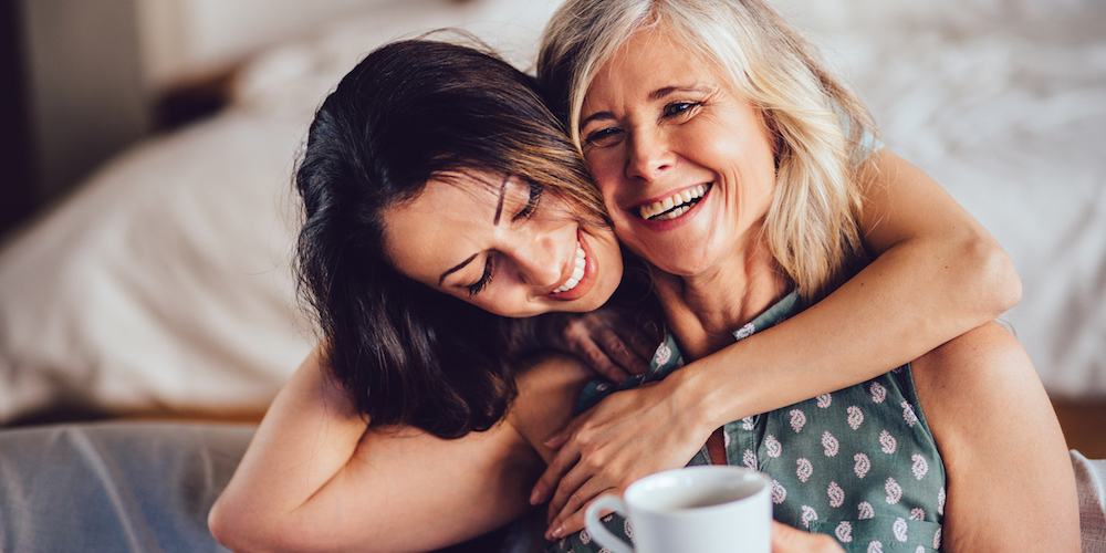 Beautiful adult granddaughter hugging beautiful senior grandmother while sitting on the sofa dinking coffee