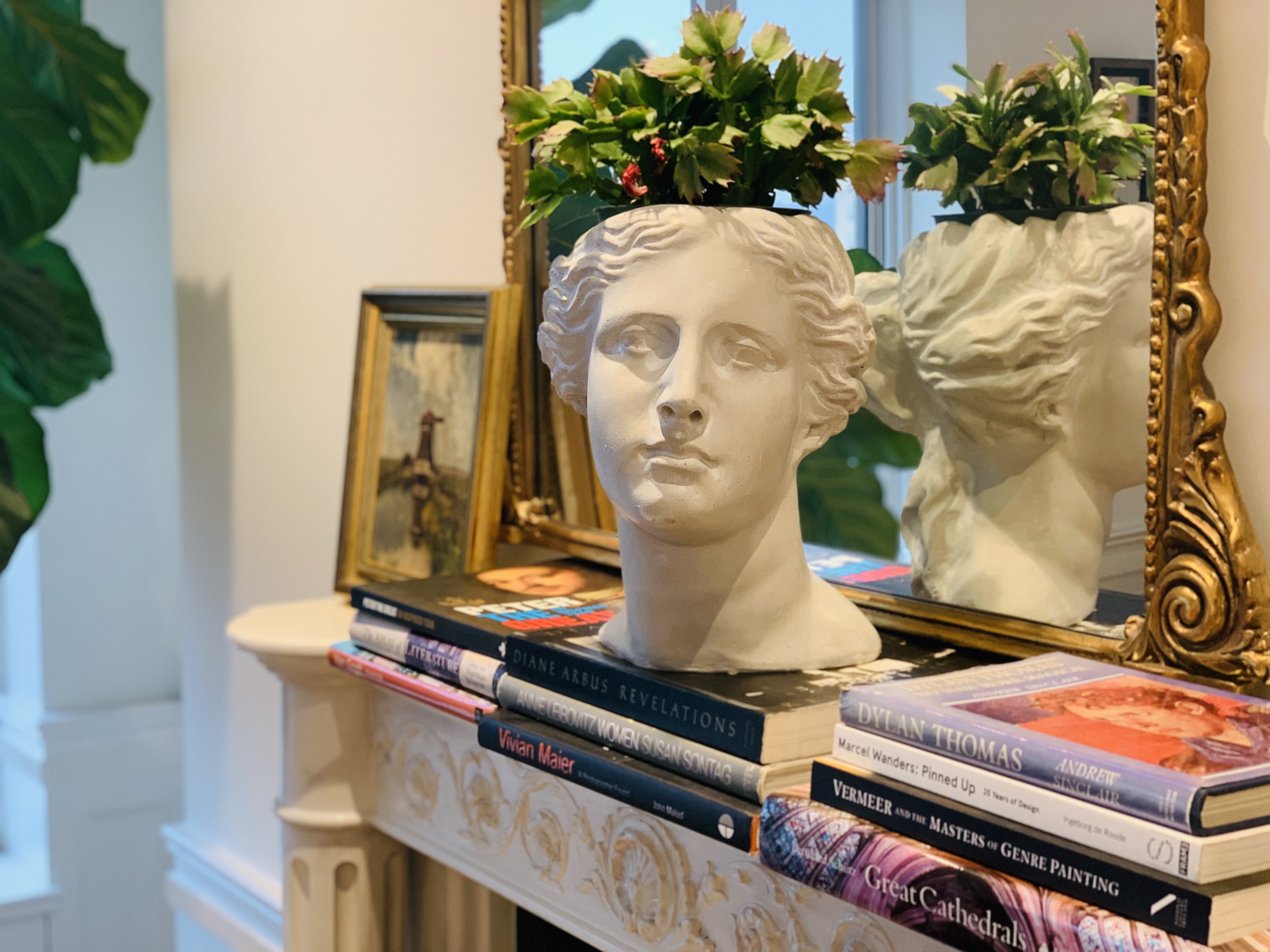 Planter bust on top of stack of coffee table books in front of mirror.