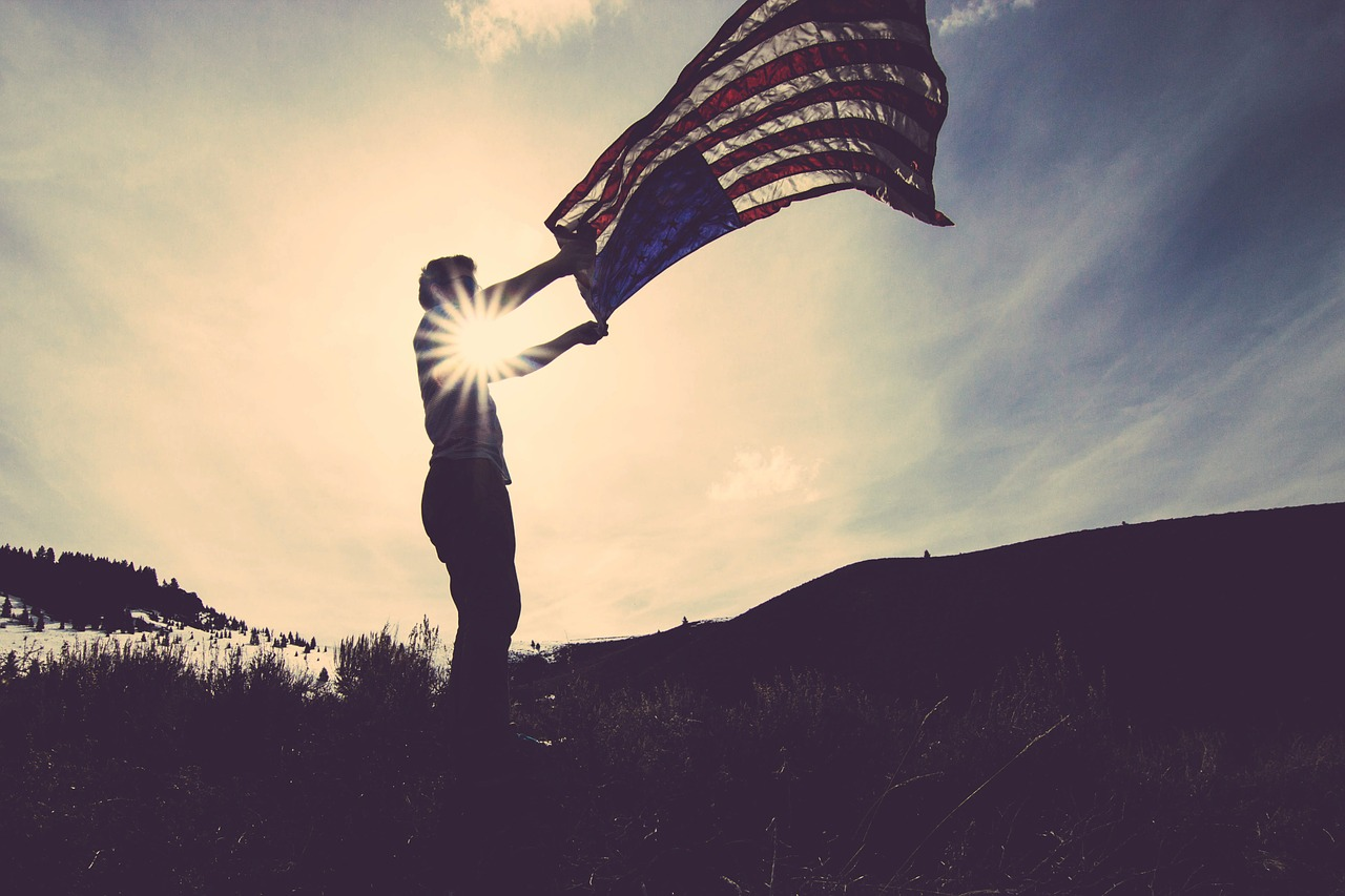A person holding the American flag on a hill