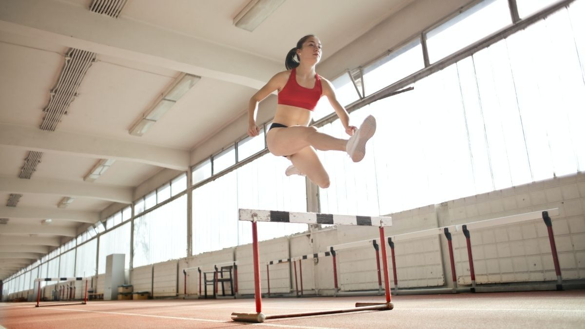 A young woman running and jumper over a hurdle