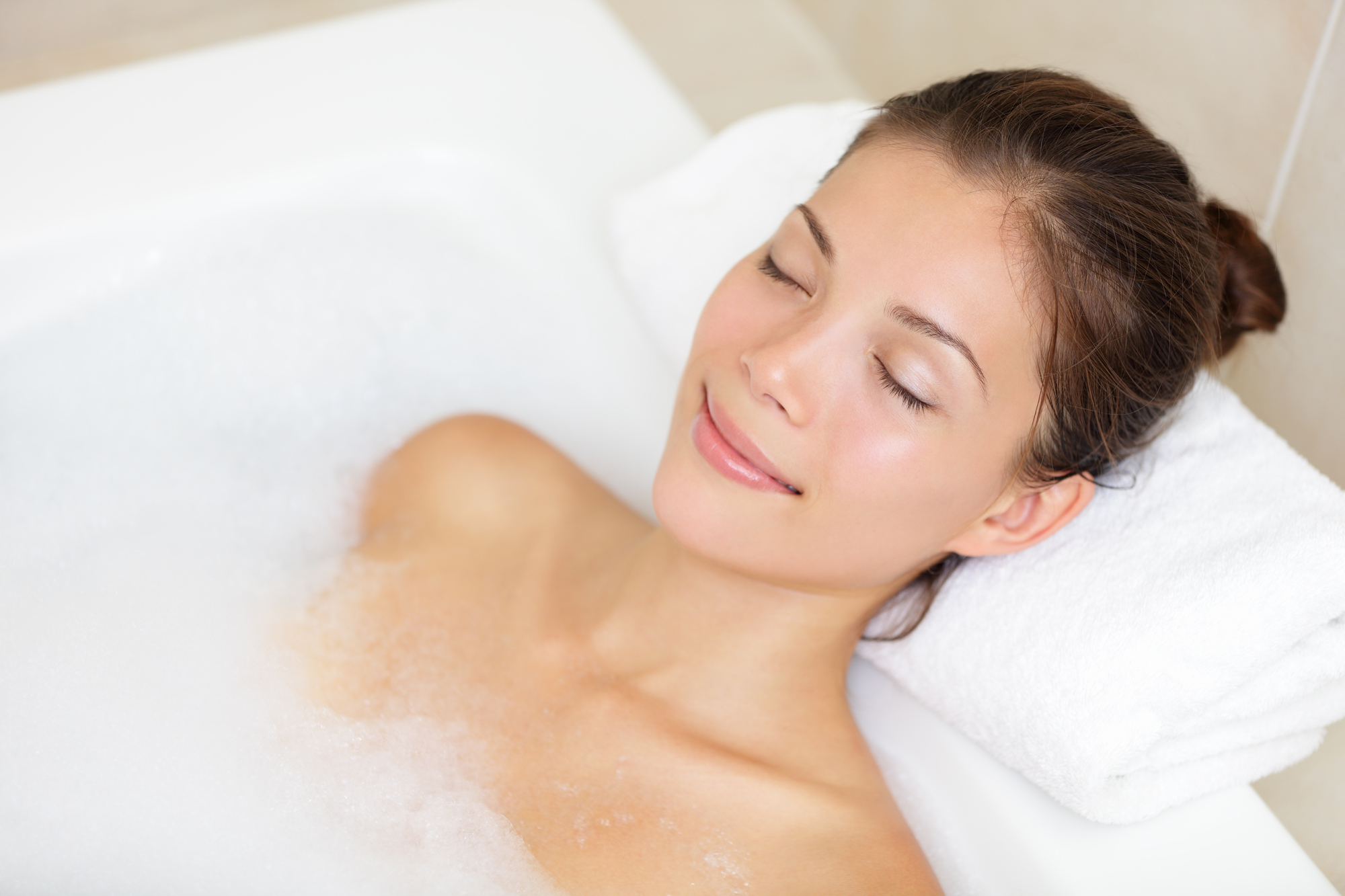 Bathing woman relaxing in bath smiling relaxing with eyes closed. Multicultural Asian / Caucasian young woman in bathtub.