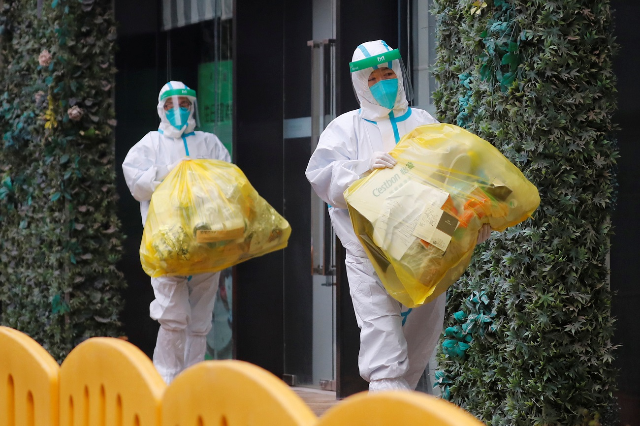 People in protective suits walk outside the hotel where members of the World Health Organisation (WHO) team tasked with investigating the origins of the coronavirus (COVID-19) pandemic are quarantined, in Wuhan, Hubei province, China January 28, 2021. REUTERS/Thomas Peter