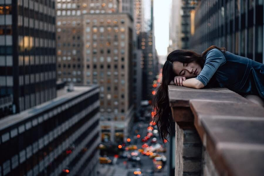 woman slumped over cityscape ledge looking depressed dealing with stress in nursing