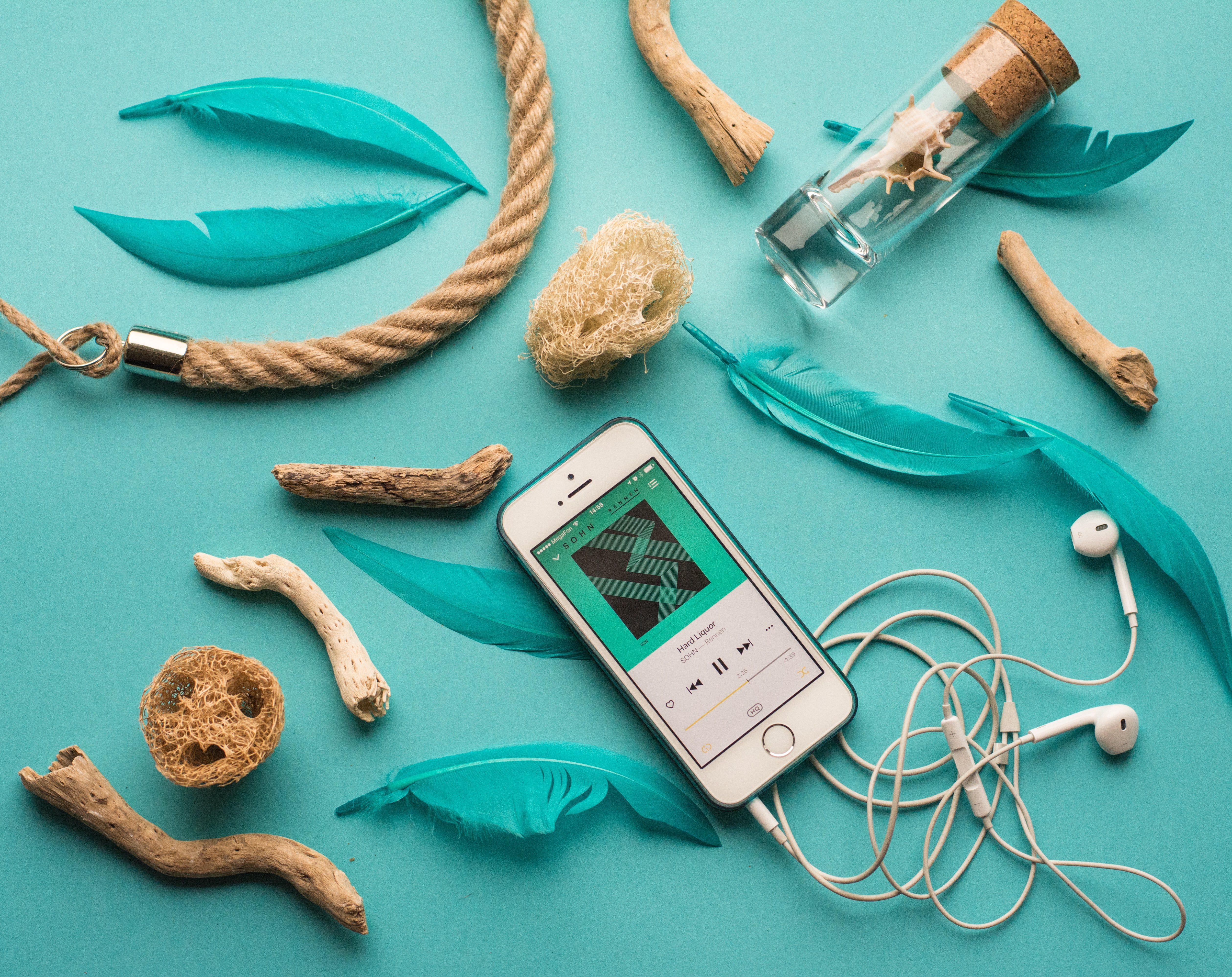 a smart phone playing a sound file with earphones attached on a background of items from the sea