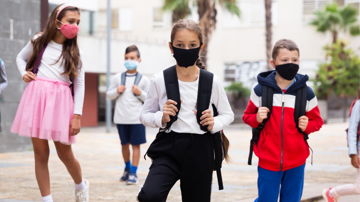 Image of kids heading to school with masks on faces