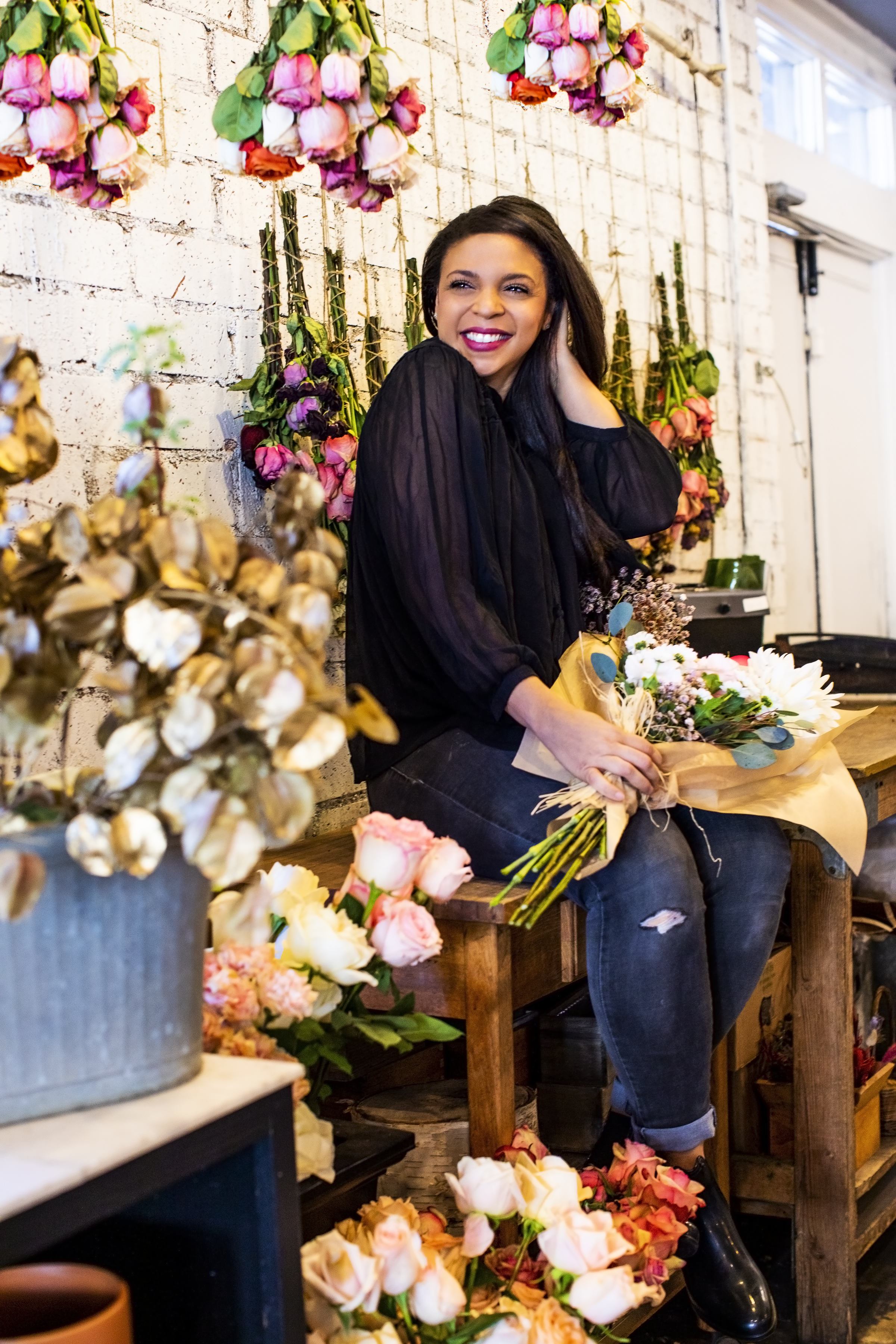 Dr. Sandra Colton-Medici sitting on bench surrounded by flowers in flower shop for Spring 2021.